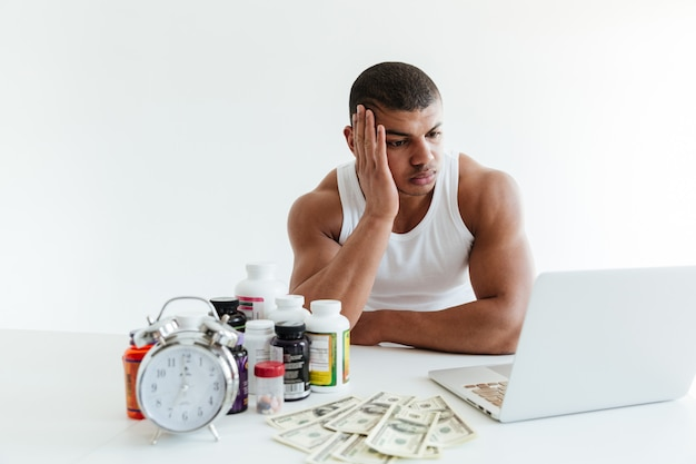 Droevige jonge sportman dichtbij geld en sportvoeding die laptop met behulp van