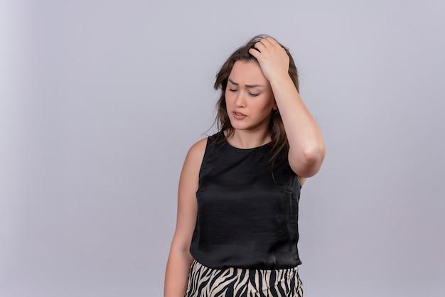 Droevige jonge vrouw die een zwart hemd draagt, grijpt het hoofd op een witte muur