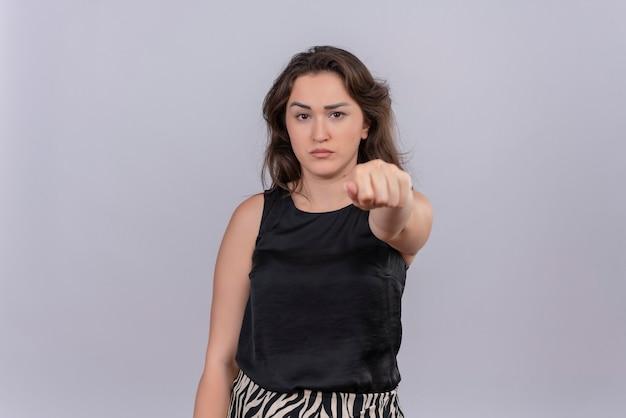 Droevige jonge vrouw die een zwart hemd droeg, stak haar vuist naar voren op een witte muur