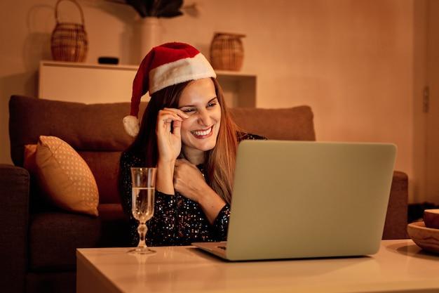 Droevige jonge vrouw, gekleed in een kerstman-hoed die een videogesprek voert met haar familie om kerstmis te vieren. concept van eenzaamheid, gescheiden gezin, sociale afstand en kerstmis.