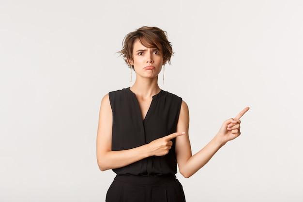 Droevige jonge vrouw klaagt, wijst met de vingers recht op de banner en mokkend boos, wit.