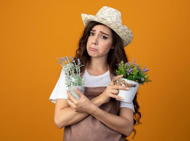 Droevige jonge vrouwelijke tuinman in uniform die tuinieren hoed draagt die bloempotten houdt die op oranje muur met exemplaarruimte worden geïsoleerd