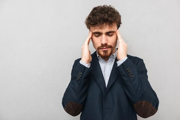Droevige jonge zakenman die kostuum draagt dat zich geïsoleerd over grijs bevindt, met hoofdpijn