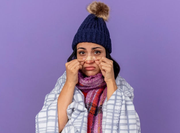 Droevige jonge zieke vrouw die de wintermuts en sjaal draagt die in plaid wordt verpakt die voorzijde bekijkt die gips op neus zet die op purpere muur wordt geïsoleerd