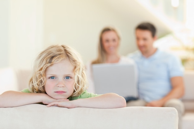 Droevige jongen met ouders op de achtergrond
