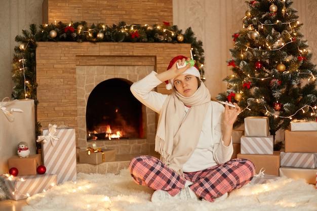 Droevige kerstdagen voor zieke vrouw thuis, vrouw draagt huiskleding en rode hoed zit op de vloer met gekruiste benen, kijkt naar de camera, raakt haar voorhoofd met de hand met keelspray, toont thermometer.