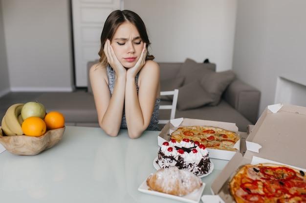 Droevige krullende vrouw die cake tijdens dieet bekijkt. blonde prachtige vrouwelijke model poseren met fruit en pizza.