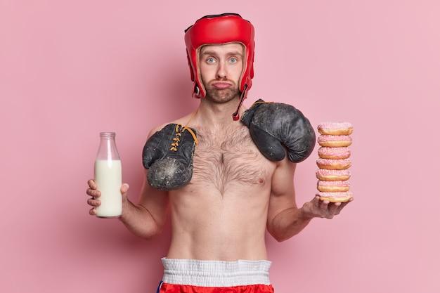 Droevige magere mannelijke bokser draagt hoed en boksbossen rond de nek houdt stapel donuts en fles melk vast.