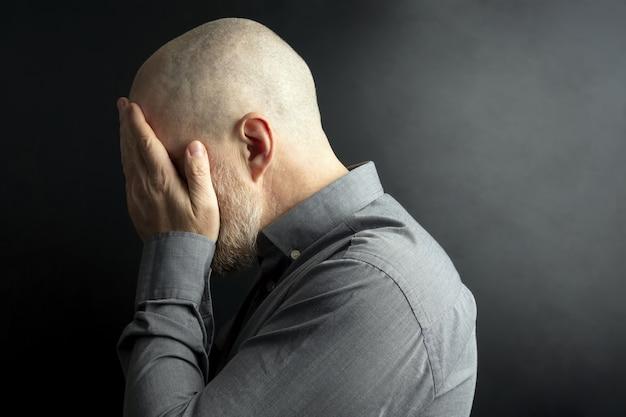 Droevige man met zijn handen gesloten gezicht wendde zich af van het licht
