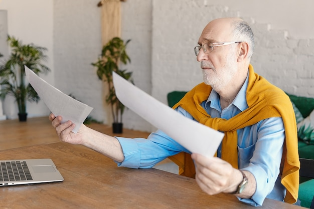 Droevige mannelijke ingenieur van in de zestig die formele kleding en bril draagt die aan een houten bureau met generieke laptop zit, documenten in zijn handen houdt, gefrustreerd raakt. baan, beroep en stress concept
