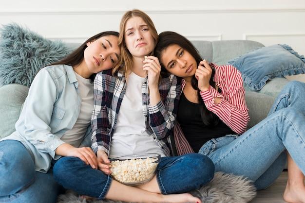 Droevige meisjes die op bank zitten en popcorn eten en grimassen trekken