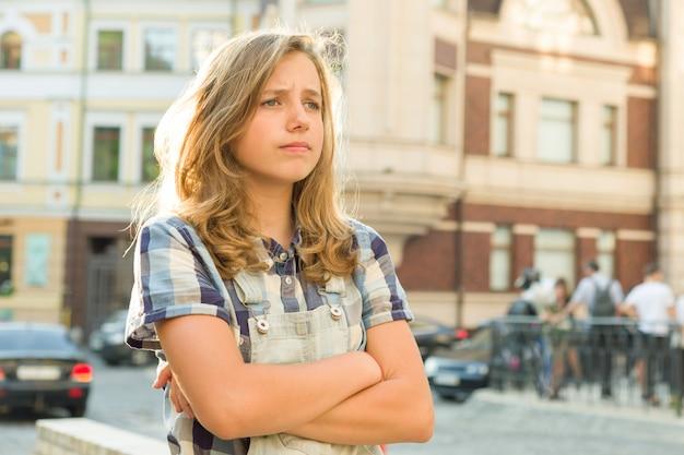 Droevige meisjestiener met wapens die op een stadsstraat worden gekruist