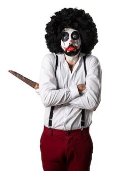 Droevige moordenaar clown met mes