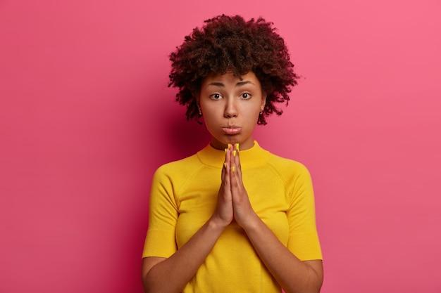 Droevige, ongelukkige afro-amerikaanse vrouw heeft een smekende uitdrukking, houdt de handpalmen tegen elkaar gedrukt, smeekt om gunst, draagt een felgele t-shirt, heeft een hopeloze blik, smeekt om verontschuldiging, heeft je hulp nodig, smeekt