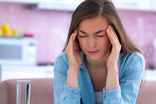 Droevige ongelukkige beklemtoonde jonge vrouw die aan hoofdpijn thuis lijdt. migraine en lichamelijke vermoeidheid voelen