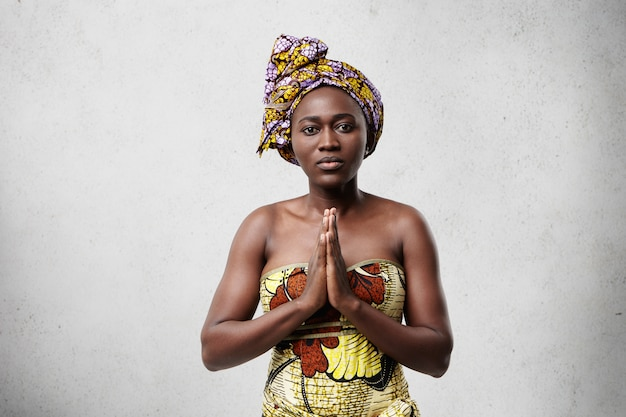 Droevige, ongelukkige dame met een donkere huidskleur die traditionele afrikaanse kleding draagt die de handpalmen tegen elkaar drukt, zich zorgen maakt terwijl ze bidt voor vrede, liefde en vrijheid in de wereld. concept van bidden en overweging