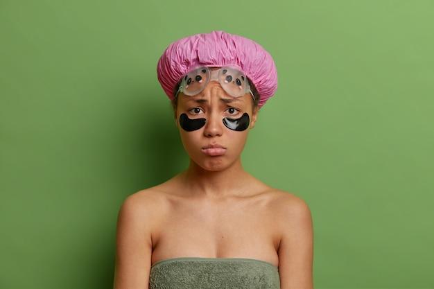 Droevige, ongelukkige jonge afro-amerikaanse vrouw heeft mokkend gezichtsuitdrukking past schoonheidsvlekken onder de ogen toe om wallen te verminderen die in een badhanddoek worden gewikkeld die over groene muur wordt geïsoleerd