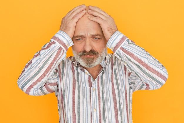 Droevige, ongelukkige oudere man met grijze baard die uitdrukking heeft benadrukt, de handen vasthoudt op zijn kale hoofd, zich depressief en eenzaam voelt, door verdriet wordt getroffen. boos senior man die lijdt aan hoofdpijn
