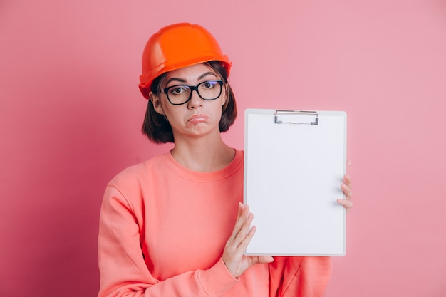 Droevige ongelukkige teleurgestelde bouwer van de vrouwenarbeider houdt wit bord leeg tegen roze achtergrond. helm bouwen.