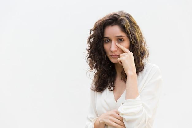 Droevige ongelukkige vrouw die tranen verwijderen uit gezicht