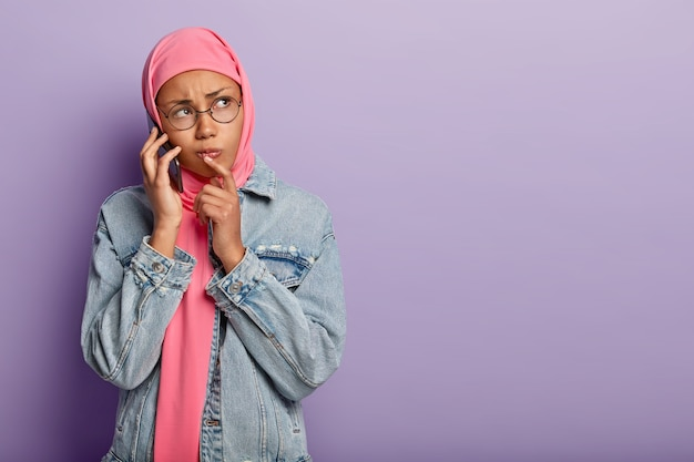 Droevige ontevreden vrouw met een donkere huid, gehuld in roze hijab, draagt een spijkerjasje, een ronde bril