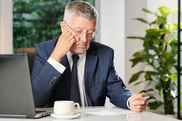 Droevige oude zakenman die contractvoorwaarden met zakenpartner leest