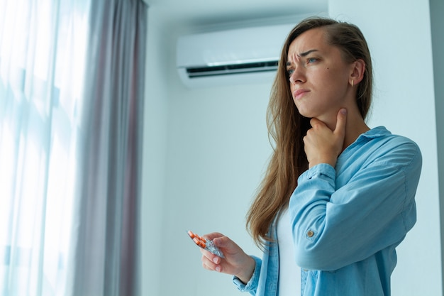 Droevige, overstuur vrouw werd verkouden door de airconditioner en leed aan keelpijn