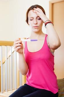 Droevige serieuze vrouw met zwangerschapstest