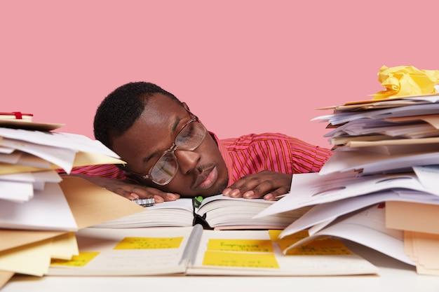 Droevige, slaperige, overwerkte mannelijke wetenschapper leunt met zijn hoofd op tafel, moe van wetenschappelijk werk, bestudeert papers, schrijft in blocnote