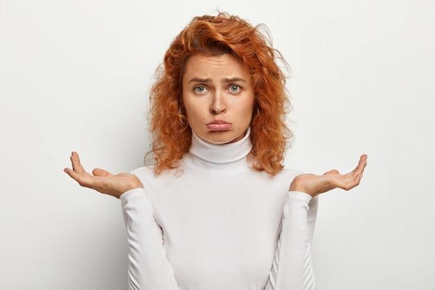Droevige sombere roodharige vrouw streelt de onderlip, neemt een serieuze beslissing, voelt twijfel en onzekerheid, spreidt de handpalmen zijwaarts, gekleed in een casual witte trui, niet zeker hoe ze haar probleem moet oplossen
