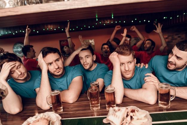 Droevige teamventilators bij bar in sportenstaaf met rood team