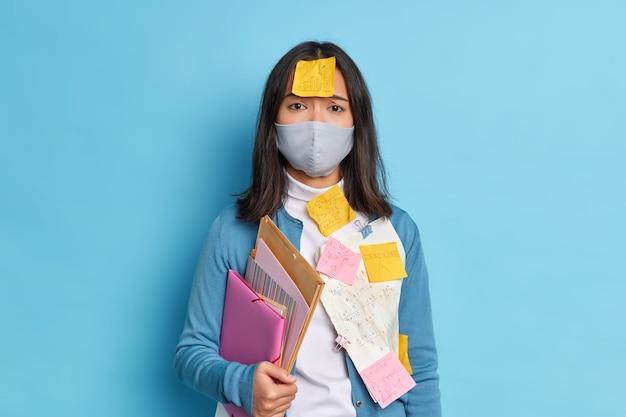 Droevige vermoeide student met donker haar heeft stickers op kleding en voorhoofd die examen gaat halen tijdens pandemische virusverspreiding.