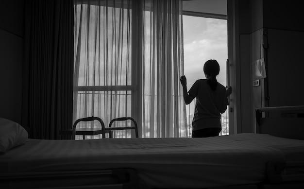 Droevige volwassen aziatische vrouw die uit venster en het denken kijkt. gestresst en depressieve jonge vrouw.