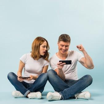 Droevige vriendin die de mobiel van haar vriend bekijkt die haar spier buigt