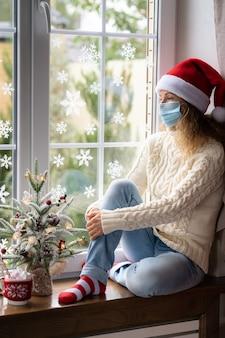 Droevige vrouw blijft thuis in de kersttijd. wintervakantie tijdens pandemisch coronavirus covid 19-concept