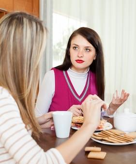 Droevige vrouw die aan vriend over haar problemen vertelt