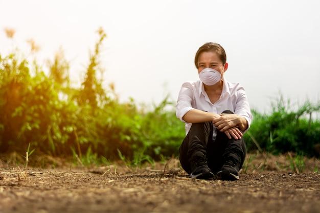 Droevige vrouw die een masker draagt bij verlaten gebied. bescherming tegen virussen, infecties, uitlaatgassen en industriële emissies.