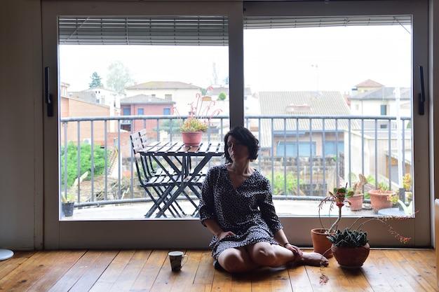 Droevige vrouw die en uit het venster zit kijkt