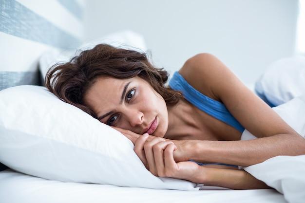 Droevige vrouw die op bed ligt