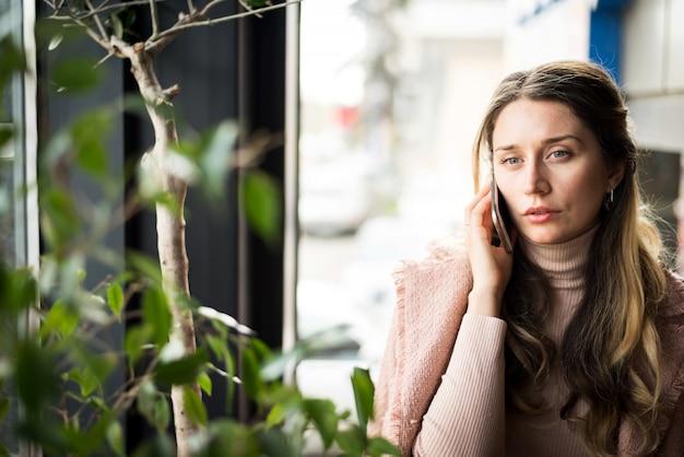Droevige vrouw die op de telefoon spreekt