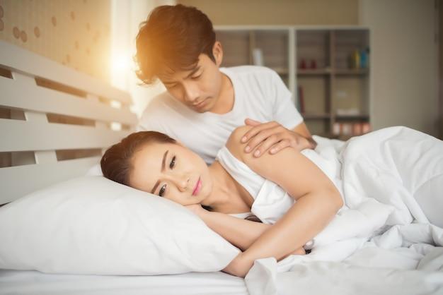 Droevige vrouw en boos haar vriend op het bed
