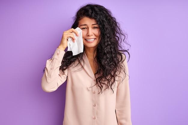 Droevige vrouw veegt af met een servet en huilt geïsoleerd over paarse muur