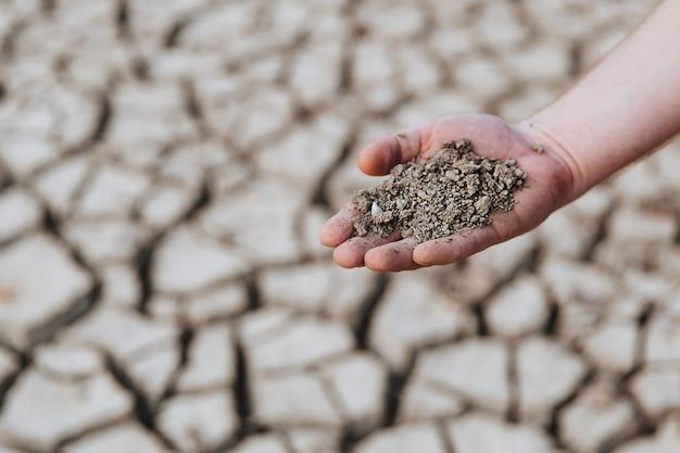 Droge aarde in de hand van een man tegen de achtergrond van een opgedroogde grond.