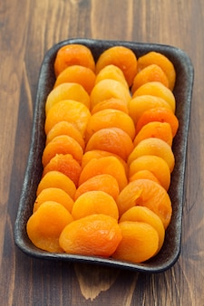 Droge abrikoos op zwarte plastic schotel