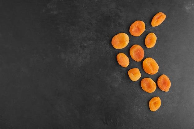 Droge abrikozen verspreid over de zwarte achtergrond.