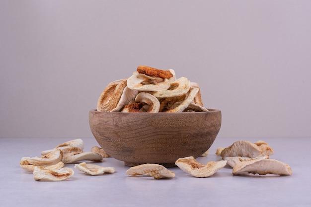 Droge appelschijfjes in een houten beker op een grijze ondergrond