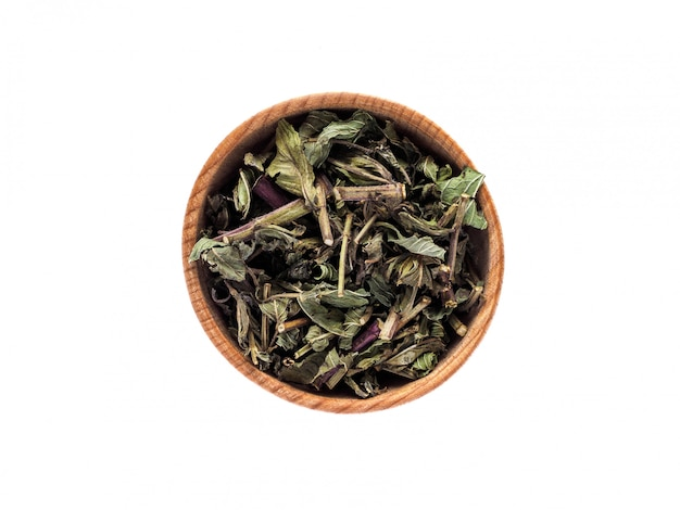 Droge bladeren van mentha-piperita in een houten kop op een wit