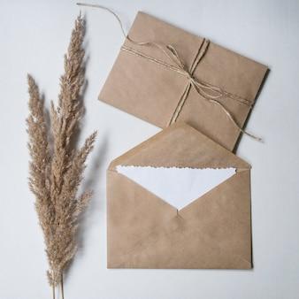 Droge bloem en kraftpapier-enveloppen op een witte achtergrond.