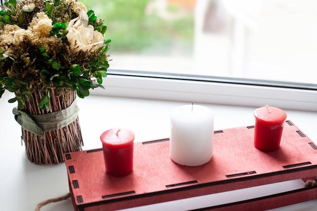 Droge bloemen en witte, rode kaarsen, een rode houten kist voor het raam.