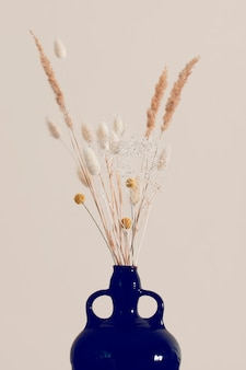 Droge bloemen in een vaas op een beige achtergrond.